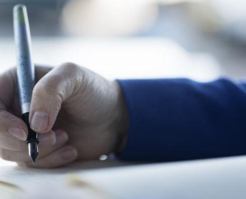 Schrijvende hand met blauwe mouw